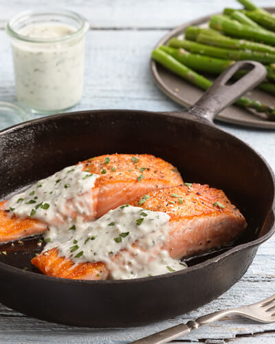 Salmon topped with creamy tarragon seafood sauce in an iron skillet