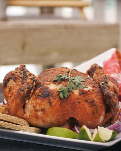 A whole tandoori chicken on a platter with naan