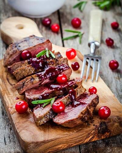 filet of beef with cranberry sauce on a serving platter